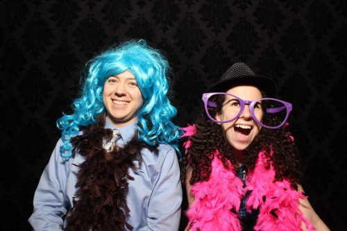 Ryan and Sharon at Photo Booth. Ryan is wearing a blue haired wig, and Sharon has on a bright pink boa with purple sunglasses.