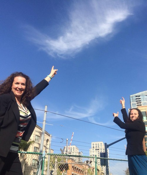 Image of Sharon and Dana in San Diego at CSUN pointing to clouds