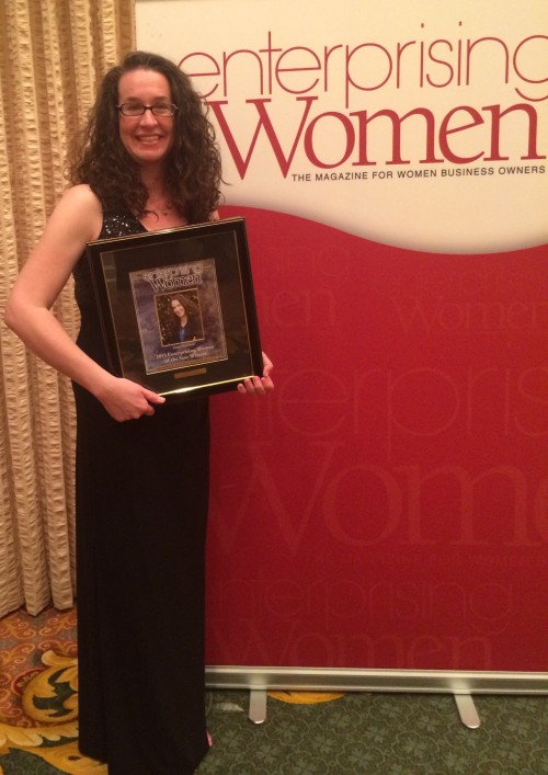Dana Marlowe holding a plaque from the Enterprising Women Awards