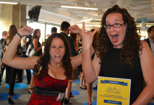 Sharon and Dana making silly faces and flexing with Dana's Trending 40 Award