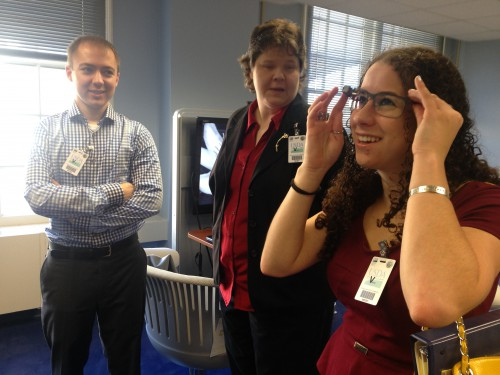 Sharon trying on Google Glass with coworkers nearby