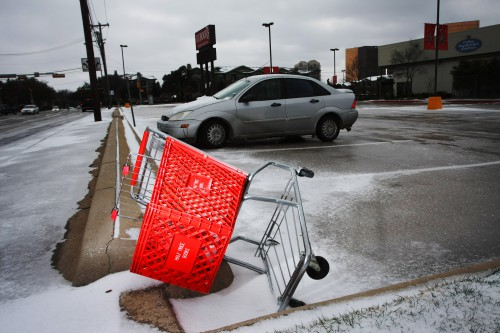 Image of an over-turned red shopping cart in a parking lot.