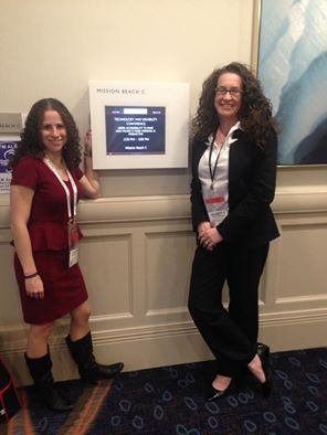 Image of Sharon and Dana outside of the presentation room at the CSUn conference, pointing to the session sign