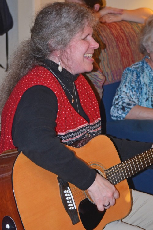 Photo of Anna Dresner seated, playing the guitar