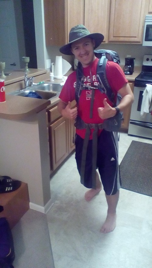 Ryan in full outdoor camping gear, including a backpack and a hat, in his kitchen