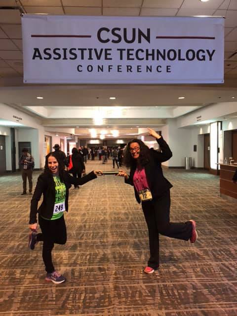 Sharon and Dana, both wearing race bibs, and passing a baton under the CSUN Assistive Technology sign.